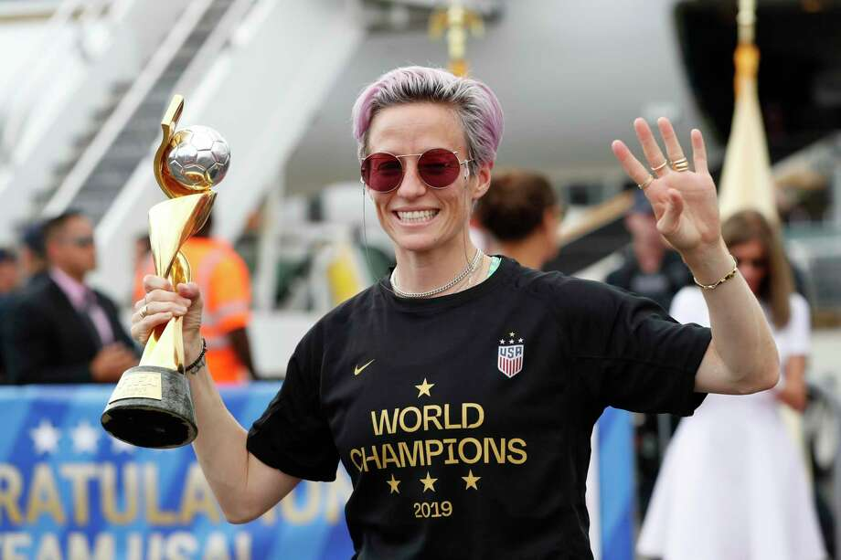 United States women's soccer team member Megan Rapinoe holds the Women's World Cup trophy as she celebrates in front of the media after arriving at Newark Liberty International Airport, Monday, July 8, 2019, in Newark, N.J. (AP Photo/Kathy Willens) Photo: Kathy Willens, STF / Associated Press / Copyright 2019 The Associated Press. All rights reserved.