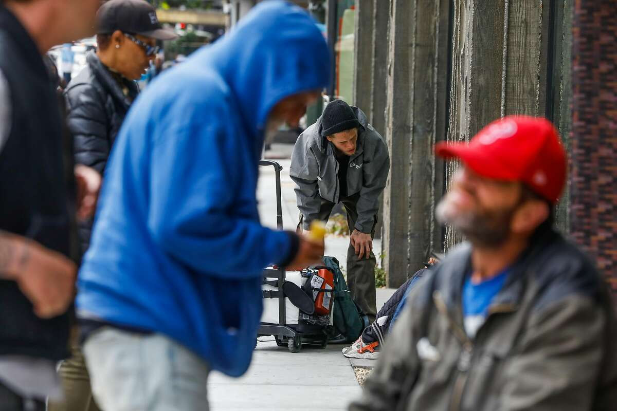 Department of Public Housing outreach worker Nick Lindley (center) chats with a homeless woman (not visible) in the Tenderloin in San Francisco, California, on Wednesday, June 26, 2019.