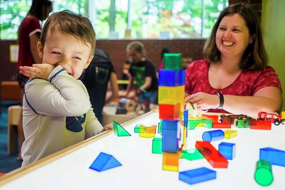 Graydon Voogd of Midland, 2, laughs after knocking over a tower of blocks while Roxanne Taylor watches on Monday afternoon at Grace A. Dow Memorial Library. (Katy Kildee/kkildee@mdn.net)