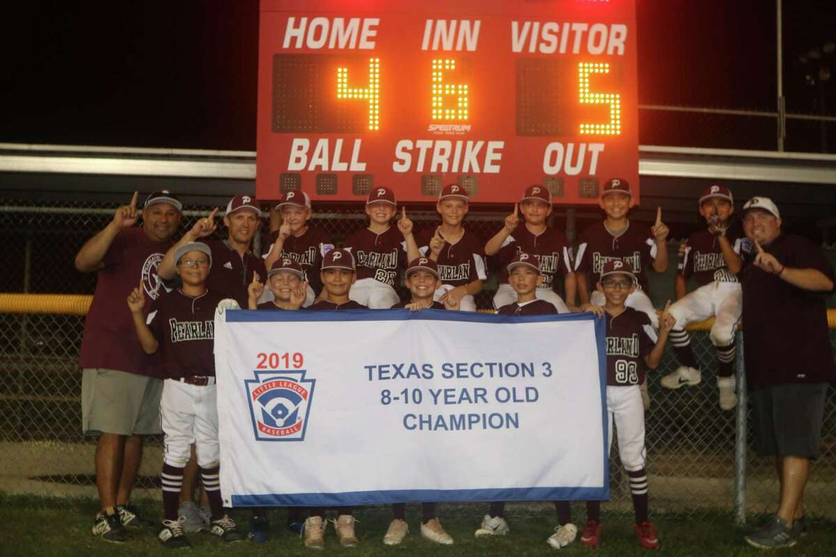 The newly-crowned Pearland East 10-year-old All-Stars pose with their championship banner Monday night.