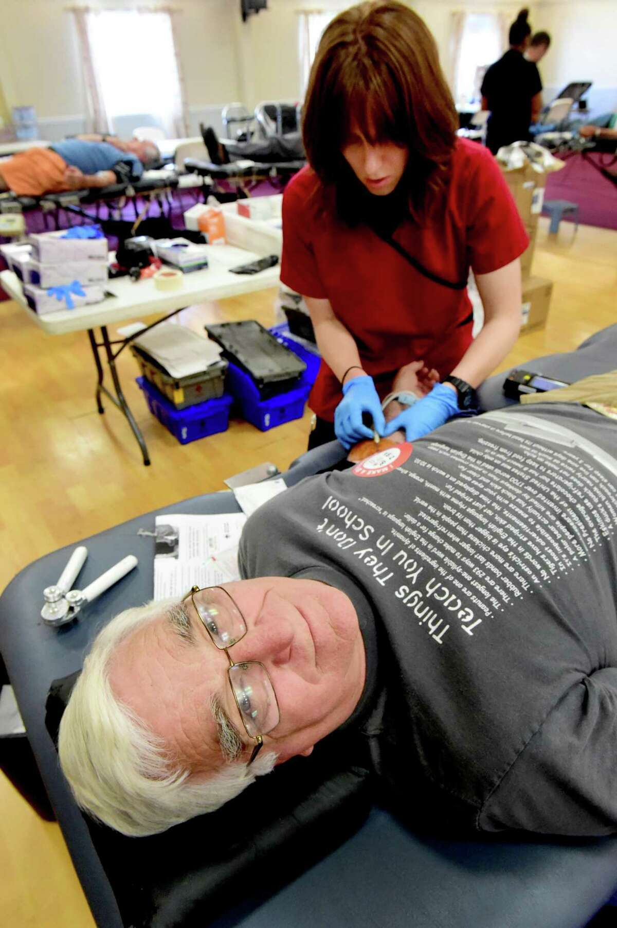 (Peter Hvizdak - New Haven Register) Blood donor William Mayer, Sr. of East Haven donates his 280th pint of blood with the American Red Cross Wednesday, July 13, 2016 at the Knights of Columbus Hall in Guilford with the help of American Red Cross collections technician Jessica Shucks. Mayer was award a special badge that honors the35 gallons total he has donated since age 17.