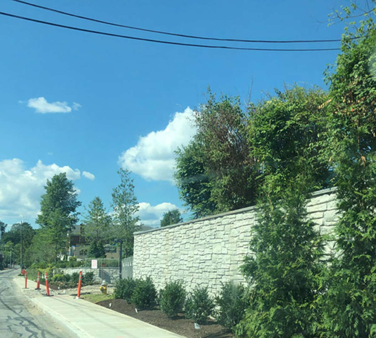 Trees, part of the planting plan to cover the faux stone walls at the Merritt Village construction project, were being put in midday Monday, June 24, 2019, in New Canaan, Connecticut. They're just enough to cover, and act as a barrier, helping the project fit more into the atmosphere of the town and not have it be a nuisance and an eyesore. Trees and other coverings, dividers and barriers are the name of the game, like they are between Grace Farms and neighbors properties. Easy solutions. Contributed photo