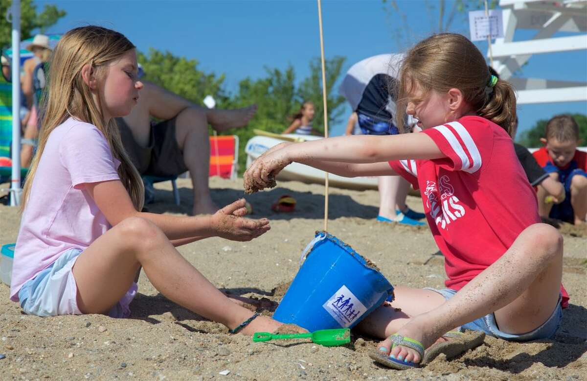 Pearl Betz, 8, left, and Katelyn Nugent, 8, both of Darien, work together on a sand project.