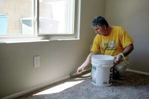 Eddy Gomez paints trim in a house that Zillow bought for resale in Phoenix, Ariz. The company sends crews to paint, carpet and landscape recently purchased properties so they can be put back on the market quickly. (Caitlin O'Hara/The New York Times)
