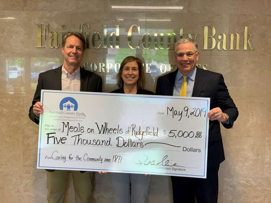 David Schneider, Chief Executive Officer of Fairfield County Bank, presents Dean Miller and Phyllis Appel, of Meals on Wheels of Ridgefield, with a $5,000 donation.