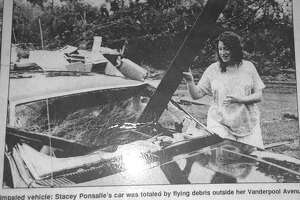A resident stands by her car after the tornado blasted its way through the borough of Bantam on July 10, 1989.