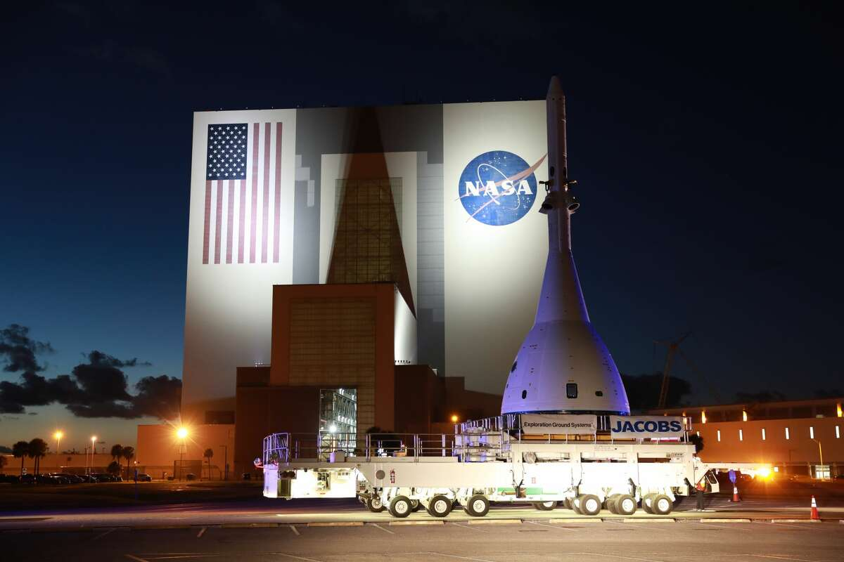 The vehicle for Orion's Ascent Abort-2 (AA-2) fight test passes by the Vehicle Assembly Building at NASA's Kennedy Space Center in Florida on its 21.5-mile-trek to Space Launch Complex 46 at Cape Canaveral Air Force Station on May 22, 2019. During AA-2, a test version of Orion will launch on a booster to more than six miles in altitude, where Orion's launch abort system will pull the capsule away to demonstrate it can keep a future crew inside safe if an emergency occurs during ascent on the Space Launch System rocket. The AA-2 elements will be stacked together at the launch pad over the next several weeks. The launch is planned for July 2 and is a critical safety test that helps pave the way for Artemis missions near the Moon, and will enable astronauts to set foot on the lunar surface by 2024.
