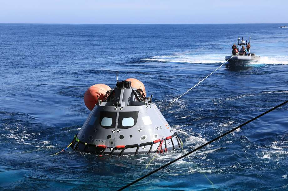 "The test version of the Orion capsule is set to be released into the open water as part of Underway Recovery Test-7, aboard the USS. John P. Murtha, on Nov. 1, 2018. During recovery operations, future astronauts aboard Orion will have the choice to stay in the capsule while it is pulled into the well deck of a U.S. Navy ship, or be pulled out immediately and put on the ""front porch"" until taken by small boat back to the ship. URT-7 is one in a series of tests to verify and validate procedures and hardware that will be used to recover the Orion spacecraft after it splashes down in the Pacific Ocean following deep space exploration missions. Orion will have emergency abort capability, sustain the crew during space travel and provide safe re-entry from deep space return velocities. (Kim Shiflett/NASA)"