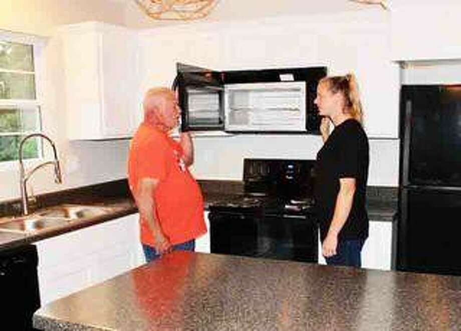 The Habitat for Humanity house at 920 Klein Ave., Edwardsville, is almost finished. Mark Hagemann, construction supervisor, shows Laura Flamuth, house recipient, some of the features in a microwave in the new kitchen. National sponsor, Whirlpool, provided the appliances and Mark's Appliance in Edwardsville did the installations. The House Blessing has been scheduled for Sunday, July 28 at 2 p.m. Photo: Courtesy Of Habitat For Humanity