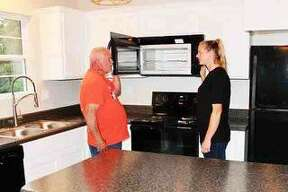 The Habitat for Humanity house at 920 Klein Ave., Edwardsville, is almost finished. Mark Hagemann, construction supervisor, shows Laura Flamuth, house recipient, some of the features in a microwave in the new kitchen. National sponsor, Whirlpool, provided the appliances and Mark's Appliance in Edwardsville did the installations. The House Blessing has been scheduled for Sunday, July 28 at 2 p.m.