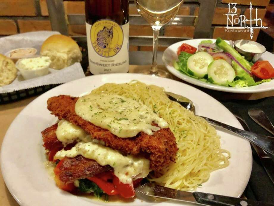 A meal at 13 North in Malta: Panko-crusted chicken with provolone, roasted red peppers, mushrooms and artichoke hearts, topped with garlic cream sauce and shaved Parmesan cheese and served with a side of angel hair pasta tossed in garlic and olive oil. Photo: 13 North Facebook Page