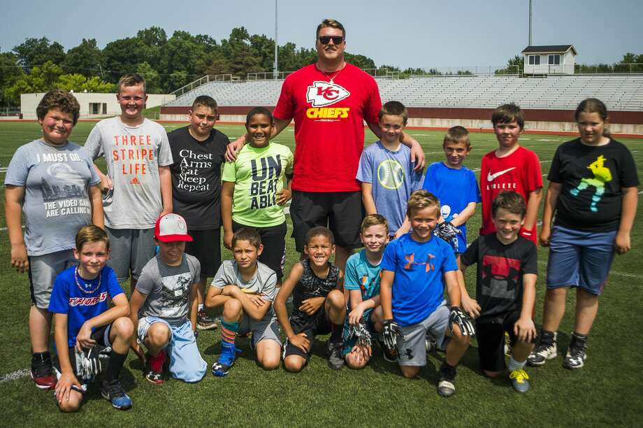 Fifth and sixth graders pose for a photo with Andrew Wylie, a Midland High graduate who now plays for the Kansas City Chiefs, during the Midland Chemics free youth football camp on Tuesday, July 9, 2019 at Midland High School. (Katy Kildee/kkildee@mdn.net) Photo: (Katy Kildee/kkildee@mdn.net)