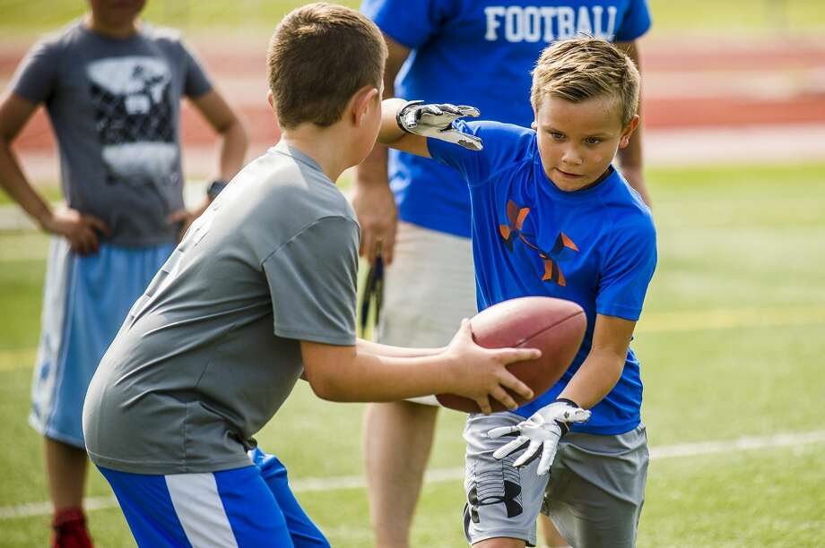 Fifth and sixth graders play football during the Midland Chemics free youth football camp on Tuesday, July 9, 2019 at Midland High School. Midland High coaches and football players taught skills to local kids during the free camp. (Katy Kildee/kkildee@mdn.net) Photo: (Katy Kildee/kkildee@mdn.net)