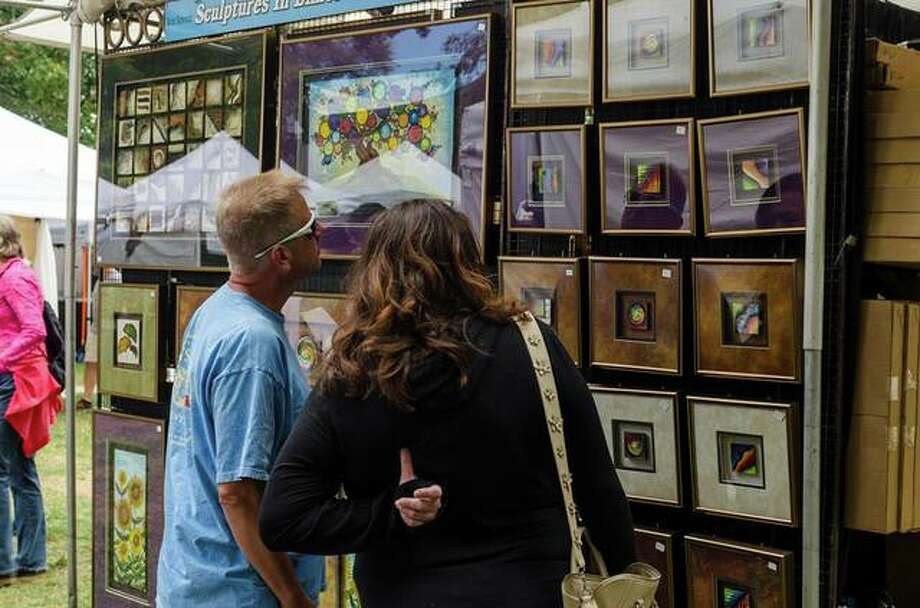 Visitors at last year's Edwardsville Arts Fair peruse the art in a booth. Photo: For The Intelligencer