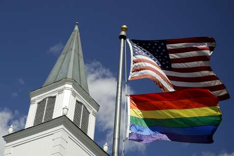 FILE - In this April 19, 2019 file photo, a gay pride rainbow flag flies along with the U.S. flag in front of the Asbury United Methodist Church in Prairie Village, Kan. A new Associated Press-NORC Center for Public Affairs Research poll shows age, education level and religious affiliation matter greatly when it comes to Americans' opinions on a prospective clergy member's sexual orientation, gender, marital status or views on issues such as same-sex marriage or abortion (AP Photo/Charlie Riedel)