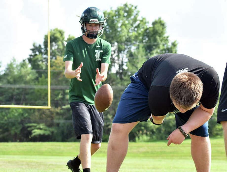 MELHS quarterback Zach Keplar takes a snap from the center during a summer practice on Monday. Photo: Matt Kamp|The Intelligencer