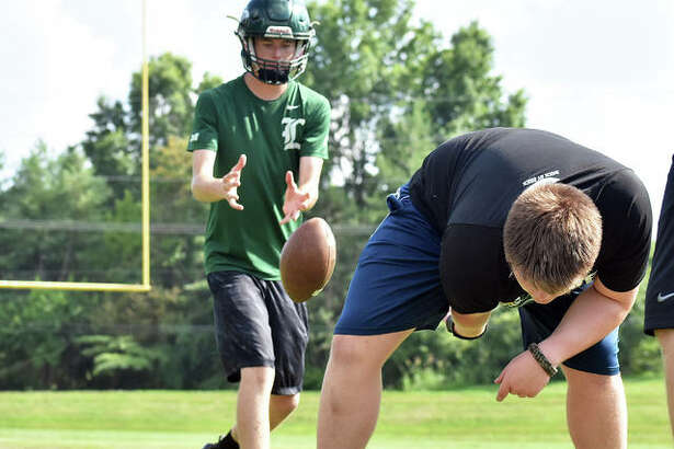 MELHS quarterback Zach Keplar takes a snap from the center during a summer practice on Monday.