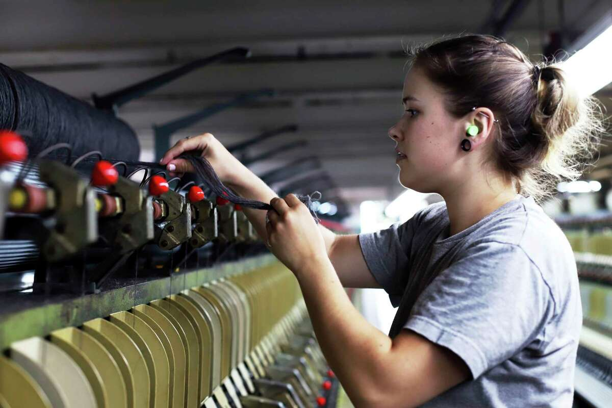 Spinning operator Sara Colburn works in July 2019 at the recently reopened American Woolen Co. mill in Stafford Springs, Conn., which supplies the U.S. Army. Connecticut manufacturers will see 35 percent of their workforce hit retirement age within a decade, prompting the need to find younger replacements in addition to any new hiring in the sector. (AP Photo/Chris Ehrmann)