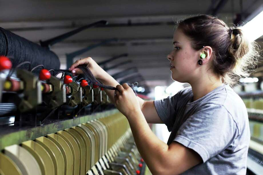 Spinning operator Sara Colburn works in July 2019 at the recently reopened American Woolen Co. mill in Stafford Springs, Conn., which supplies the U.S. Army. Connecticut manufacturers will see 35 percent of their workforce hit retirement age within a decade, prompting the need to find younger replacements in addition to any new hiring in the sector. (AP Photo/Chris Ehrmann) Photo: Chris Ehrmann / Associated Press / Copyright 2019 The Associated Press. All rights reserved.