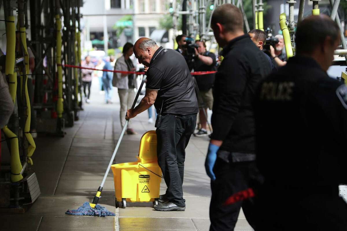 A man cleans up blood from the sidewalk outside of Nordstrom, Tuesday afternoon, where a man reportedly stabbed three people on the sidewalk, including a 77 and a 75-year-old man who were both transported to Harborview Medical Center and are in stable condition. The suspect was apprehended several blocks away. The third victim had minor injuries and refused transport to the hospital.