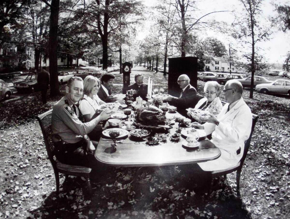 Among those to share a Thanksgiving dinner on the Village Green more than four decades ago were, clockwise, from the front left, New Milford police Chief Ted Adams; unidentified; Sylvester Craig; Father Robert Sanders from St. Francis Xavier Church; attorney Henry