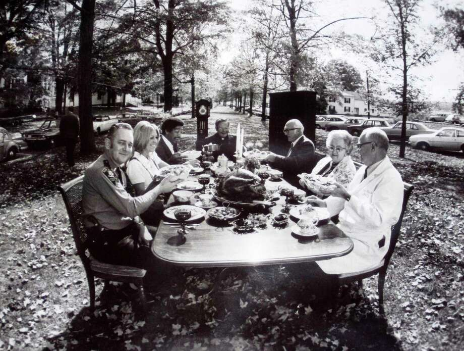 "Among those to share a Thanksgiving dinner on the Village Green more than four decades ago were, clockwise, from the front left, New Milford police Chief Ted Adams; unidentified; Sylvester Craig; Father Robert Sanders from St. Francis Xavier Church; attorney Henry ""Hank"" Anderson; Marian Carlson; and Dr. John Street. Photo: Courtesy Of New Milford Historical Society / The News-Times Contributed"