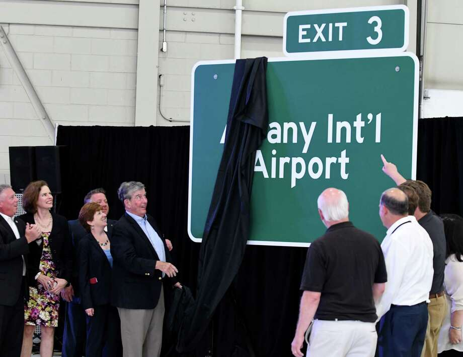 Sen. Neil Breslin pulls back the cover to reveal a sign for Exit 3 of the Northway on Tuesday, July 9, 2019, during a press conference at the Million Air hangar bay in Colonie, N.Y. Joining him were; Assemblyman John T. McDonald III, left, Assemblymember Patricia Fahy, Albany County Executive Dan McCoy and Albany Mayor Kathy Sheehan. (Will Waldron/Times Union) Photo: Will Waldron, Albany Times Union / 20047423A