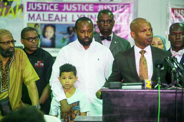 "Kenyatta Jones, whose eleven-year-old son Kamren Jones was killed in a drive-by shooting, holds onto one of his sons while listening as Deric Muhammad introduces him during a gathering of community activists speaking out against violence against children, at the SHAPE Community Center in Houston, Tuesday, July 9, 2019. The group called for a ""Cease Fire"" in the wake of many recent deaths of children."