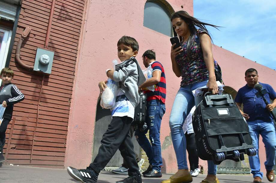 Lucia Ascencio, of Venezuela, carries a suitcase after she and her husband and two sons were returned to Nuevo Laredo, Mexico, as part of the first group of migrants sent back to Mexico's Tamaulipas state under the so-called Remain in Mexico program for U.S. asylum seekers, Tuesday, July 9, 2019. Approximately 10 migrants crossed the border Monday to seek U.S. asylum and were sent back on Tuesday to wait as their applications are processed. (AP Photo/Salvador Gonzalez) Photo: Salvador Gonzalez, Associated Press