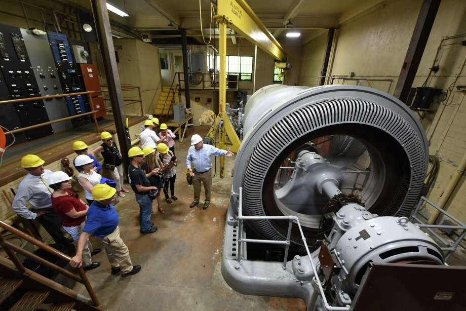 Colonie Town officials are given a tour of the Schuylerville Hydroelectric Facility turbine room by John Elmer, director of operations for  Brookfield Renewable, right, on Tuesday, July 9, 2019, in Schuylerville, N.Y. Under an innovative mechanism known as remote net metering, Colonie has agreed to a 20-year power purchase agreement with Gravity Renewables, Inc. for power produced at a Schuylerville hydroelectric facility owned and operated by Brookfield Renewable.(Will Waldron/Times Union) Photo: Will Waldron, Albany Times Union / 40047435A