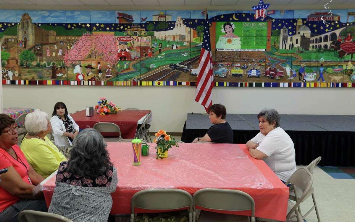 """Students in Bihl Haus Arts' Arts' GO! program gather to chat about """"South Side Pride,"""" the mural on the wall behind them. The students painted the mural for a 60-foot-wide wall in the dining room of the Elvira Cisneros Senior Center."""