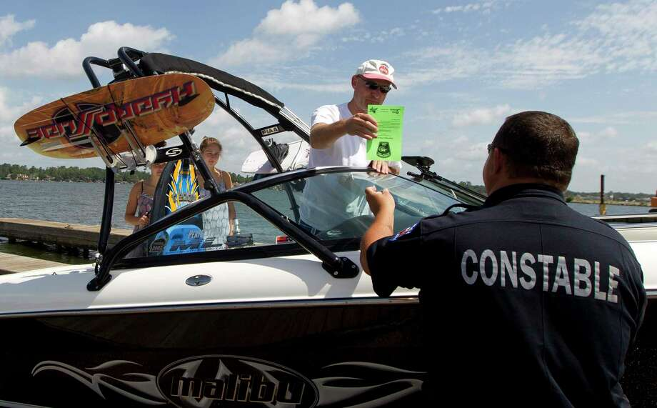 Brandon Bangerter, of The Woodlands, gets a safety check tag from Wesley McGee, with Precinct 1 Montgomery County Constable's Office, checks safety equipment before a group of boaters enjoy an afternoon on Lake Conroe, Friday, July 5, 2019, in Conroe. Photo: Jason Fochtman, Houston Chronicle / Staff Photographer / Houston Chronicle