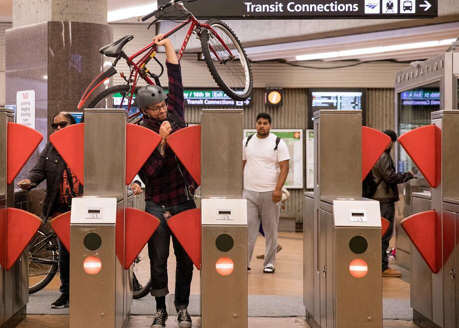 A commuter struggles to get himself and his bike through a new prototype fare gate at the Richmond BART Station in Richmond, Calif. Tuesday, July 9, 2019. Photo: Jessica Christian / The Chronicle