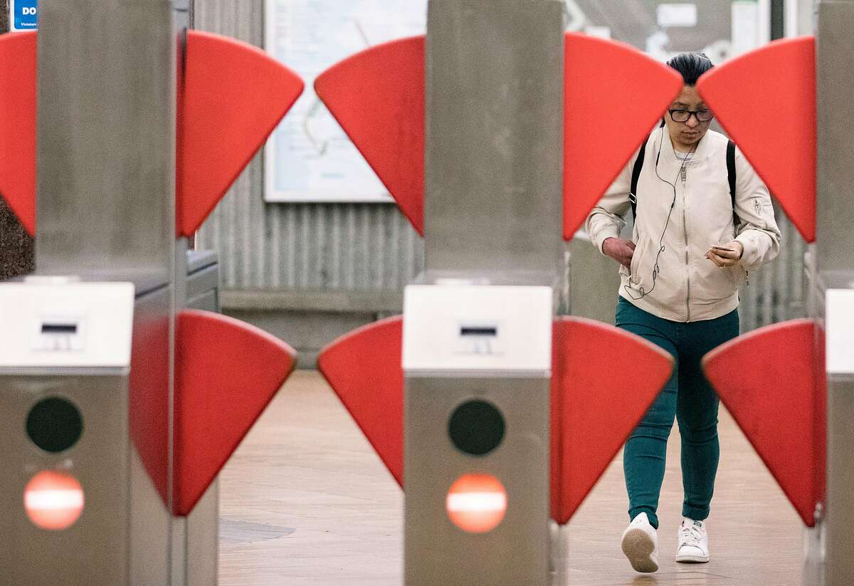 A commuter is seen through an opening between the blades of a new prototype fare gate at the Richmond BART Station in Richmond, Calif. Tuesday, July 9, 2019.