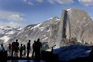 ** ADVANCE FOR SUNDAY, JAN. 28 ** Visitors view Half Dome from Glacier Point at Yosemite National Park in 2005. Millions flock here to admire a landscape of soaring crags and plunging falls chiseled by the Merced River, but the car-bound throngs and the infrastructure needed to house and feed them are precisely what threatens the federally protected waterway.  (AP Photo/Dino Vournas)