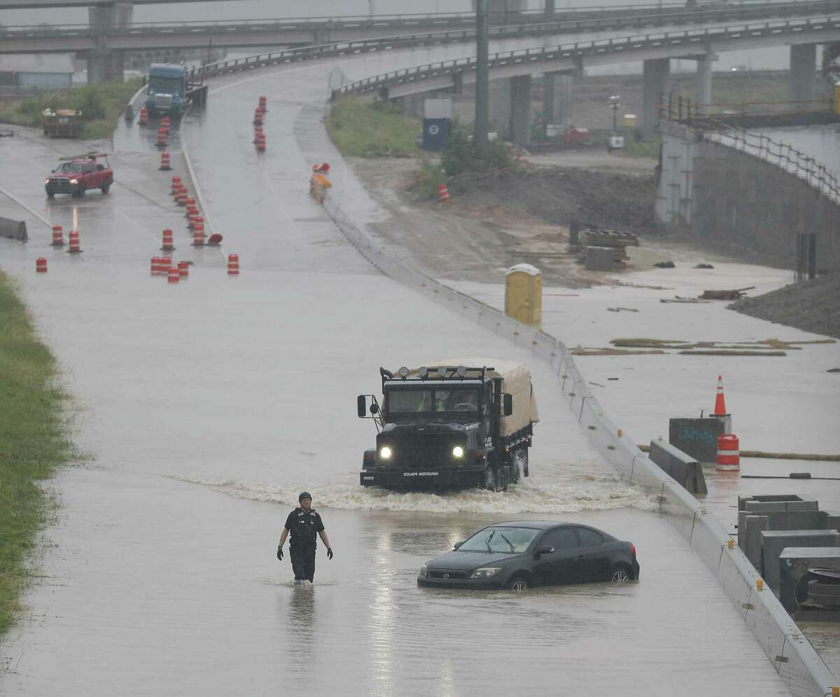 A Houston Police High Water Rescue responders checks on a vehicle stranded on the South Freeway near Holly Hall Wednesday, July 4, 2018, in Houston. ( Steve Gonzales / Houston Chronicle )
