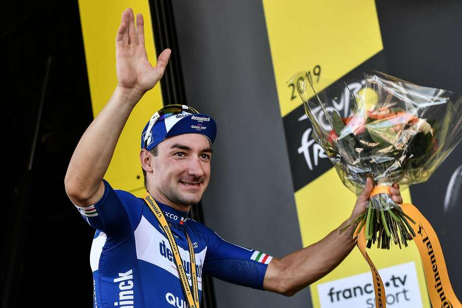 Stage 4 winner Elia Viviani of Italy, a sprinting specialist, celebrates on the podium with a bouquet of flowers. Photo: Jeff Pachoud / AFP / Getty Images