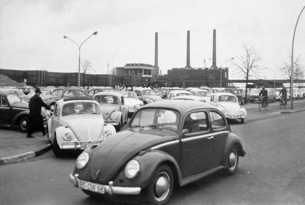 FILE - In this April 27, 1966 file photo, Volkswagen workers drive their Beetle cars from the parking lot on their way home at the end of a days work at the world's largest single auto plant, the Volkswagen factory (seen in background) in Wolfsburg, Germany. Volkswagen is halting production of the last version of its Beetle model in July 2019 at its plant in Puebla, Mexico, the end of the road for a vehicle that has symbolized many things over a history spanning eight decades since 1938.(AP Photo, file)