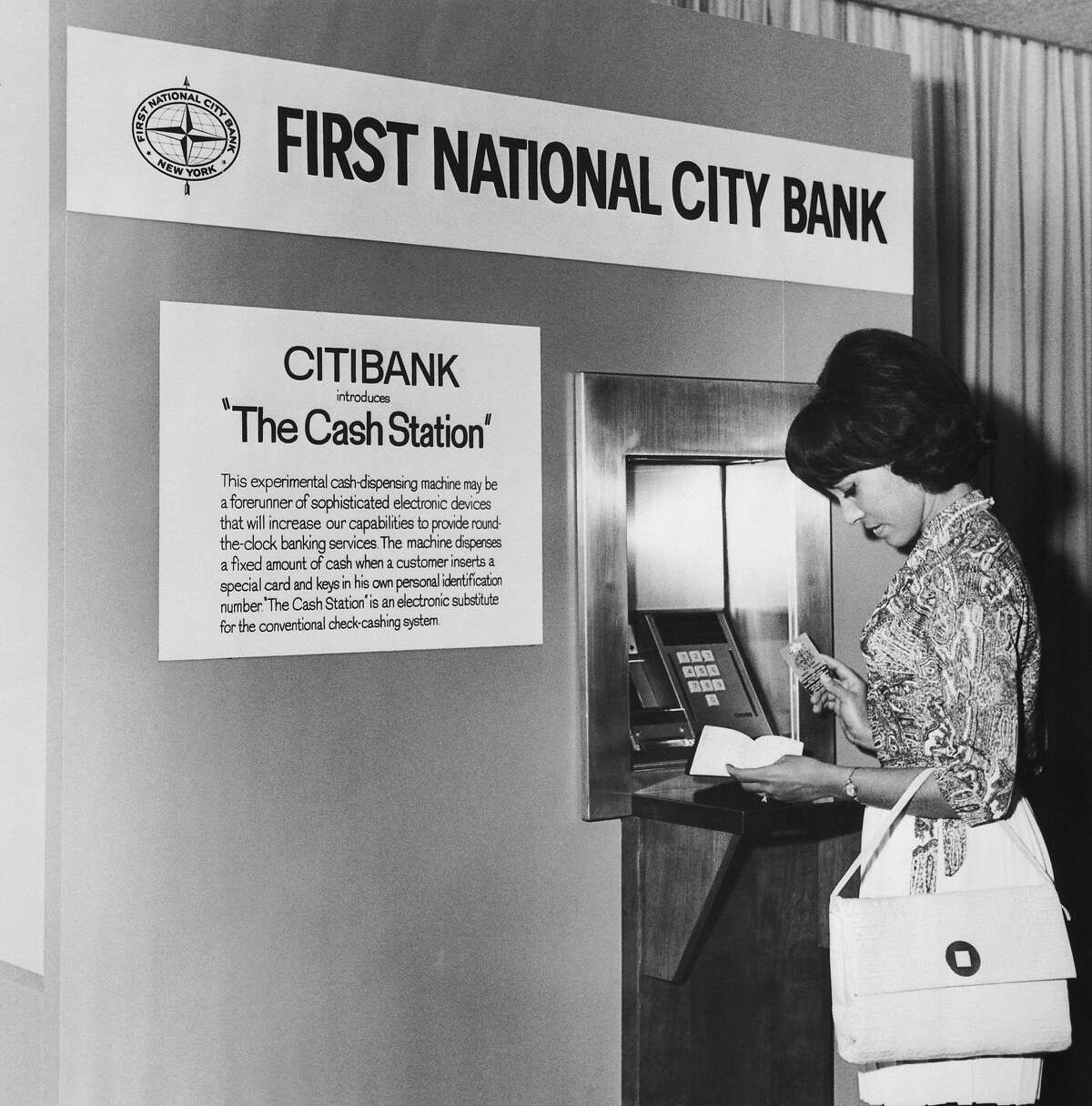 """(Original Caption) New York: A machine that, in effect, cashes checks around the clock will be put in use on an experimental basis at the headquarters of first national city bank Tuesday. The bank said it could revolutionize banking services. The bank calls it """"The Cash Station"""" because it pays out cash without the intervention of a teller. The depositor inserts a special card in a slot in the machine and at the same time keys in a confidential identification number. The machine dispenses a fixed amount of cash and records the transaction, retaining the card which is returned to the depositor with his monthly statement. Charles F. Hayward, a citibank vice-president, said the machine, made by a British firm, Chubb & Sons, is virtually temperproof. It is already being used successfully in England. Hayward said the bank would test the machine thoroughly before making any plans to inst"""