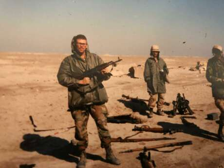 Scene from the Gulf War: Mike Glenn and a couple of his troops in Iraq. Glenn holds an AK-47 assault rifle confiscated from a prisoner.