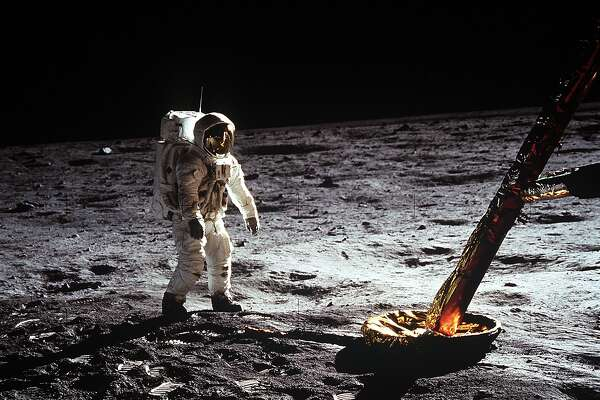 """Astronaut Edwin E. Aldrin Jr., lunar module pilot, walks on the surface of the moon near a leg of the Lunar Module during the Apollo 11 extravehicular activity (EVA). Astronaut Neil A. Armstrong, Apollo 11 commander, took this photograph with a 70mm lunar surface camera. The astronauts' bootprints are clearly visible in the foreground. While astronauts Armstrong and Aldrin descended in the Lunar Module (LM) """"Eagle"""" to explore the Sea of Tranquility region of the moon, astronaut Michael Collins, command module pilot, remained with the Command and Service Modules (CSM) """"Columbia"""" in lunar orbit."""