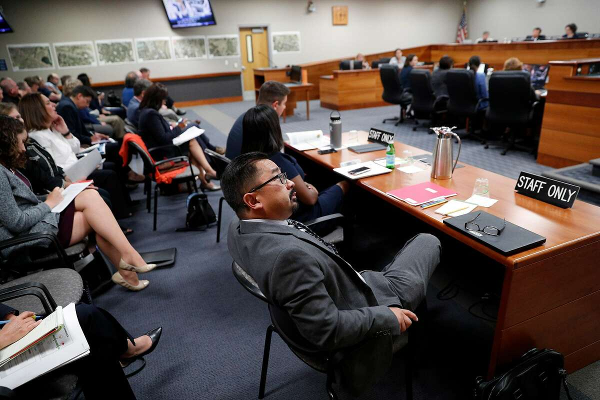 Fremont Urban Initiatives Manager, Clifford Nguyen listens to Police Chief Kimberly Peterson speak during a meeting discussing possible locations for a homeless navigation center at City Council chambers in Fremont, Calif., on Tuesday, July 9, 2019. Fremont is considering locations to open a new navigation center in their city for the homeless. In September, the council will determine one specific location for the center-- which will house Fremont residents and other Alameda County residents. Residents agree that the city should do more to help the homeless, as long as its