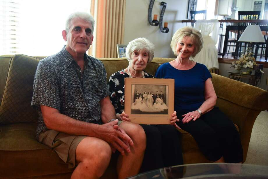 Edith Bonsonto, holding her wedding photo, sits with her son Gerald and her daughter-in-law Caroline. Her wedding dress was made from her late husband's WWII parachute. Thursday, June 27, 2019, in Orland Park.  (Gary Middendorf/Daily Southtown/TNS) Photo: Gary Middendorf, MBR / TNS / Chicago Tribune