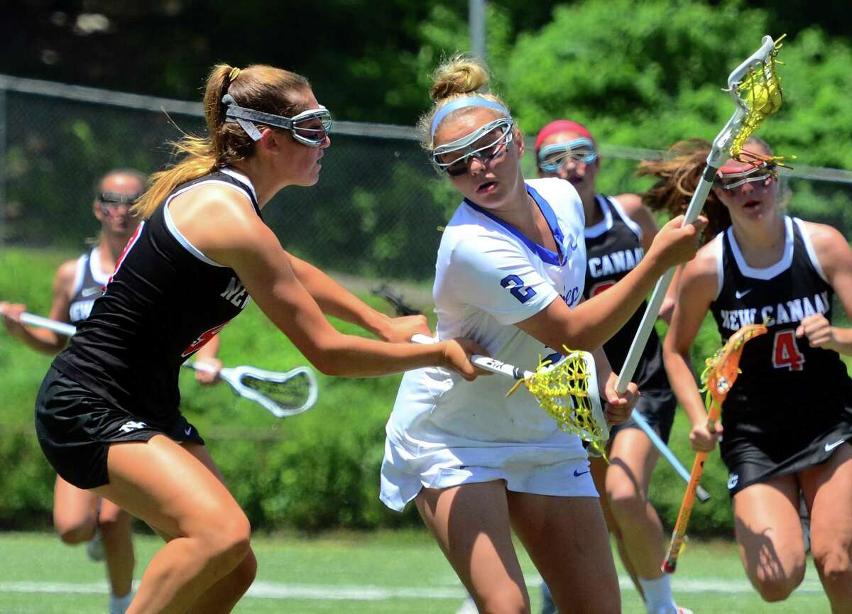 Darien's Ashley Humphrey (2) drives the ball as New Canaan's Katelyn Sparks defends during the Class L girls lacrosse final in Milford on Saturday June 8.