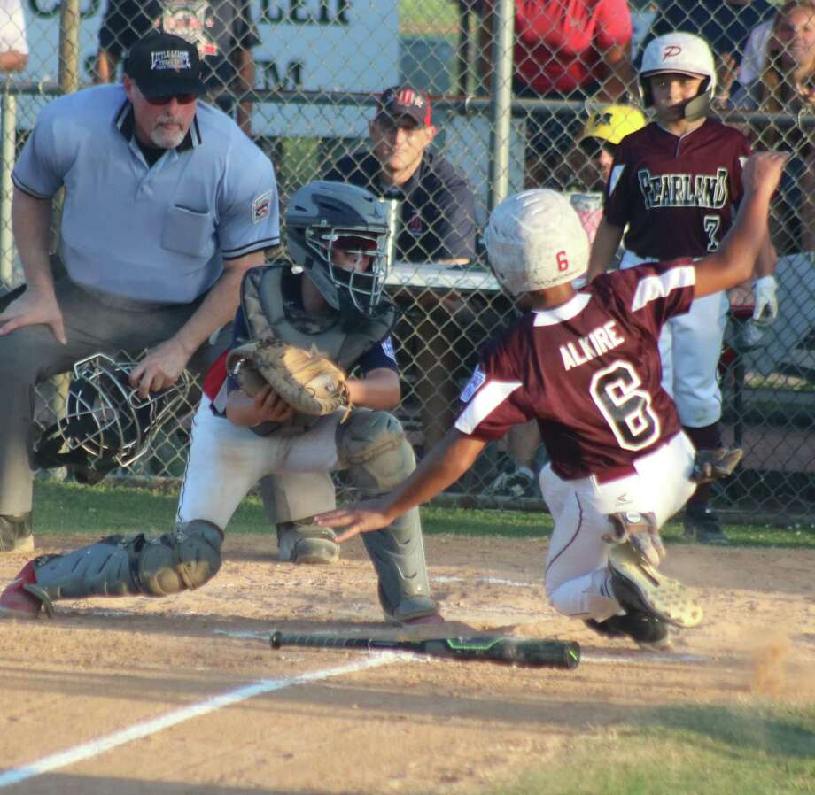 What will be the outcome of this play at the plate? Pearland East Little League's Eziekiel Alkire begins his slide to home plate while catcher Wilson Reagan looks to apply the tag. Photo: Robert Avery