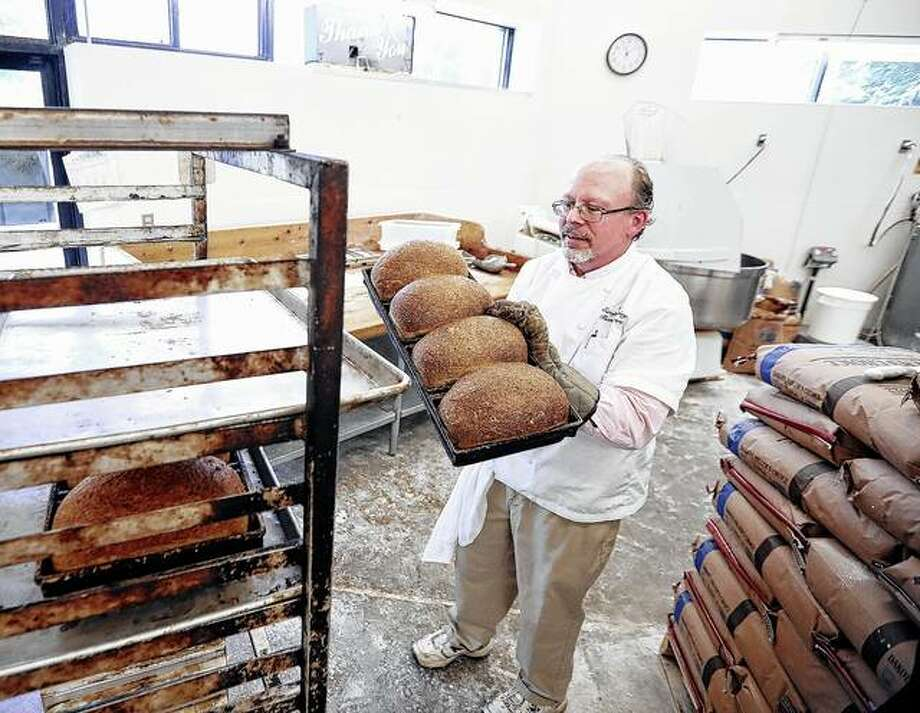 Tom Siewert, general manager of Clasen's Bakery in Middleton, Wisconsin, removes from the oven a tray of freshly baked bread made with Capital Brewery's spent grains from their Wisconsin Amber lager. Photo: Amber Arnold | Wisconsin State Journal Via AP