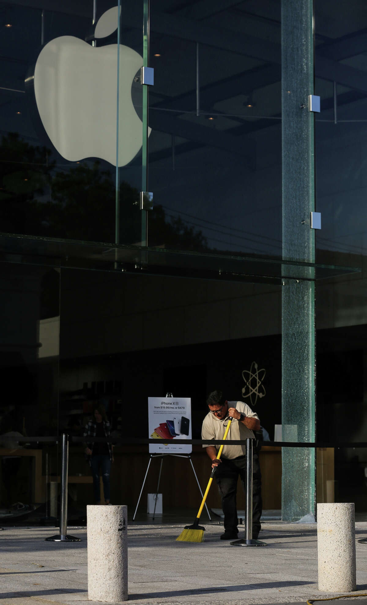 A Highland Village worker cleans up debris left from the smash and grab in which suspects drove a stolen truck into the Apple Store Wednesday, July 10, 2019, in Houston.