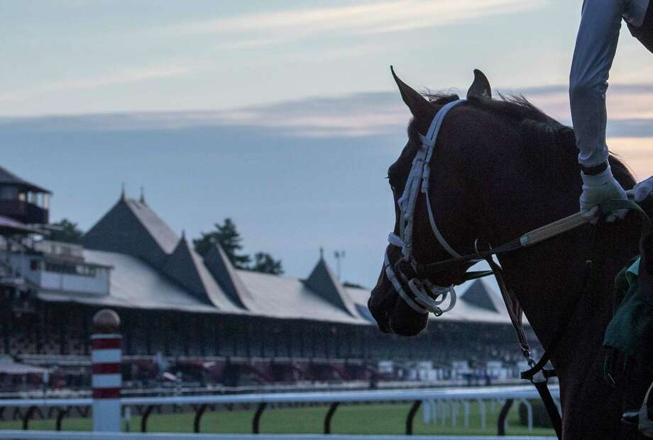 A horse from the Todd Pletcher training stable gallops goes out for exercise as the sun rises on the Saratoga Race Course Wednesday, July 10, 2019 in Saratoga Springs, N.Y.  The 2019 meeting of the Saratoga Race Course begins July 11th.   Special to the Times Union by Skip Dickstein Photo: SKIP DICKSTEIN / ©Skip Dickstein 2019
