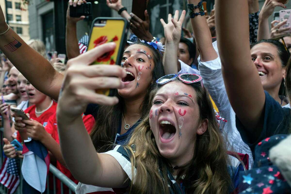 Fans celebrates as members of the the U.S. women's soccer team pass by during a ticker tape parade along the Canyon of Heroes, Wednesday, July 10, 2019, in New York. The U.S. national team beat the Netherlands 2-0 to capture a record fourth Women's World Cup title.