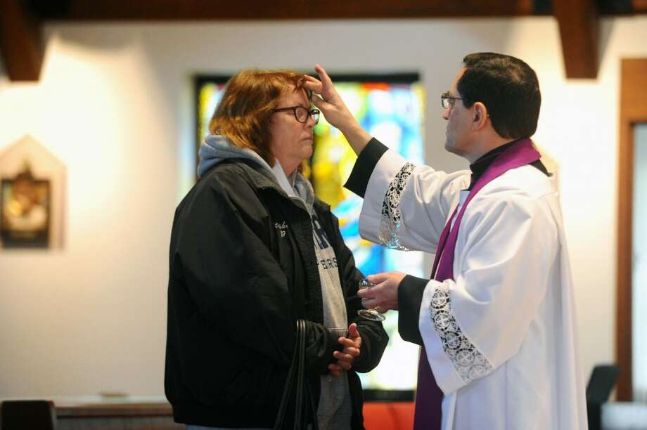 Msgr. Kevin Royal places ashes on a congregants head during Ash Wednesday inside the Church of the Holy Spirit on Scofieldtown Road in Stamford on Wednesday, Feb. 14, 2018. Photo: THE RIDGEFIELD PRESS